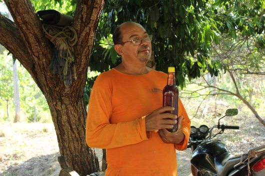 Um homem vestido de camisa de manga comprida segura uma garrafa de 900ml de mel. Ao fundo, há um tronco de árvore e uma moto preta.