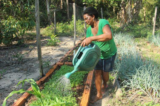 Dona Osmarina molha os canteiros com um regador grande verde